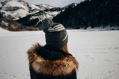Woman in Black and Brown Winter Jacket Facing the Snow Capped Mountain Royalty Free Stock Photography