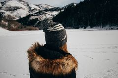 Woman in Black and Brown Winter Jacket Facing the Snow Capped Mountain Royalty Free Stock Photo