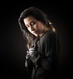Woman in Black. Brunette woman in black standing in front of black backdrop, clasping her hands to her chest and looking down with a serious, sad expression on Stock Photography