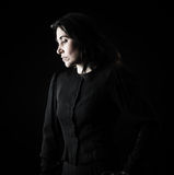 Woman in Black. Brunette woman in black standing in front of black backdrop, with a hand on her hip and looking down with a serious, sad expression on her face Royalty Free Stock Photos
