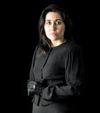 Woman in Black. Brunette woman in black standing in front of black backdrop, with her hands held together and looking at the camera with a serious expression on Royalty Free Stock Images