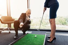 A woman in a black business suit plays golf in the office. An old man in a business suit helps her. The old man, in a strict business suit, teaches his secretary Stock Photo