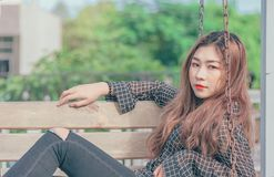 Woman in Black Button-up Long-sleeved Shirt Sitting on Brown Swing Bench stock images