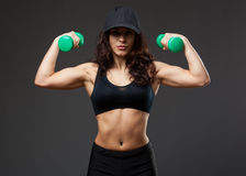 Woman in a black cap holding dumbbells royalty free stock photos