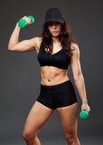 Woman in a black cap holding dumbbells royalty free stock images