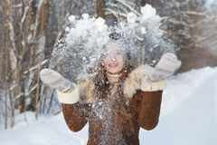 Woman in a black cap throwing snowball Stock Photography