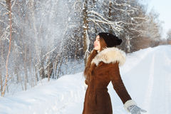 Woman in a black cap throwing snowball Stock Image