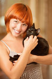 Woman with black cat. Young beautiful red-haired smiling woman has control over fluffy black cat stock photos