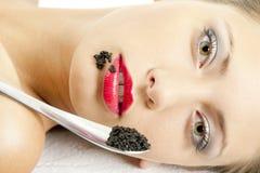 Woman with black caviar Stock Photos