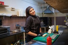 Woman in black chef prepares sushi restaurant. 1 Royalty Free Stock Photography
