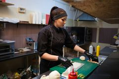 Woman in black chef prepares sushi restaurant. 1 Royalty Free Stock Image