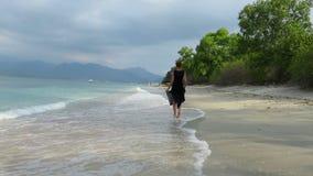 Woman in black chiffon dress walking by the sea stock video