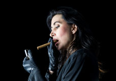 Woman in Black with Cigar and Lighter. Brunette woman in black dress and black gloves standing in front of a black backdrop, getting ready to light a cigar Royalty Free Stock Images