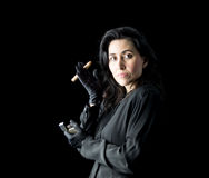 Woman in Black with Cigar and Lighter. Brunette woman in black dress and black gloves standing in front of a black backdrop, holding a cigar in one hand and a Stock Images