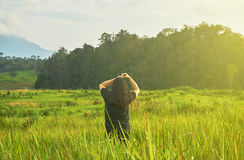 A woman in black cloth is standing in the grass field. Royalty Free Stock Photography