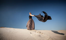 Woman with black cloth walking on sand dunes Stock Photo