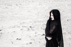 Woman in a black clothes in a desert Stock Photos