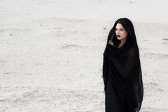 Woman in a black clothes in a desert Royalty Free Stock Photo