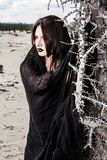 Woman in a black clothes near the dry tree. Young woman in a black clothes near the dry tree royalty free stock image