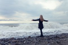 Woman in a black coat on the beach Royalty Free Stock Photo