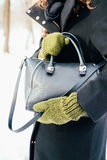 Woman in the black coat and green gloves holds a handbag close-up Royalty Free Stock Image