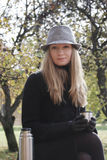 Woman in black coat and hat with cup Stock Photos