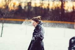 Woman In Black Coat Hit With Snowball On The Head Stock Photos