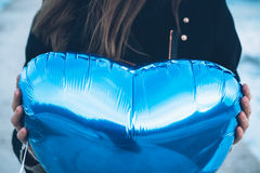 Woman in black coat holding a balloon in the shape of a heart. On a background of the sea close-up Stock Photography