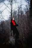Woman in black coat and red scarf sitting in cold dark forest Stock Photo