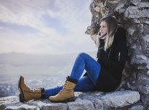 Woman in Black Coat Sitting on Rock royalty free stock photos