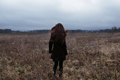Woman in black coat standing in cold autumn field Royalty Free Stock Photo