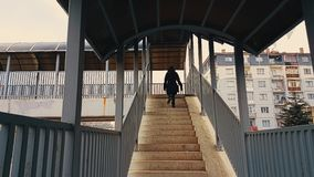 Woman with black coat walking up the stairs of the footbridge stock video footage