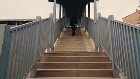 Woman with black coat walking up the stairs of the footbridge stock footage