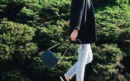 Fashion spring autumn. Woman black coat white jeans, leather bag stock images