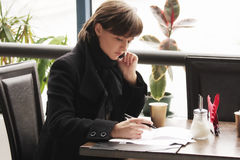 Woman in black coat working in cafe. Young woman in black coat working in cafe with papers Royalty Free Stock Photo