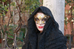 Woman in a black costume and golden mask posing at the Venice carnival in Italy Stock Photo