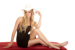 Woman black cover up white hat sit on red looking Stock Photography
