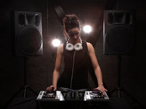 Woman in black dj with white headphones on her neck playing music on mixer with light beam effects. Loudspeakers on background. pa. Young woman dj in headphones Royalty Free Stock Photos