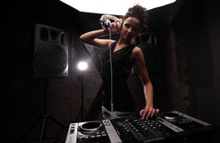 Woman in black dj with white headphones playing music on mixer with light beam effects. big Loudspeakers on background. Young woman dj in headphones playing Stock Photography