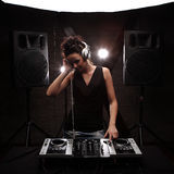 Woman in black dj with white headphones playing music on mixer w. Young woman dj in headphones playing music on mixer on table Stock Photos