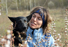 Woman with black dog. Young woman dressed in blue clothes is nearly her favorite black dog. Situation in outdoor. Bloom tree is in the foreground stock photos