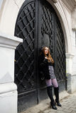 Woman and black door Stock Photography