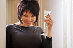 Woman in black dress. Portrait of a woman with a glass of champagne Stock Photography