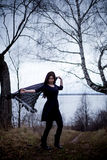 Woman in black dress dancing in cold dark forest background Royalty Free Stock Photos