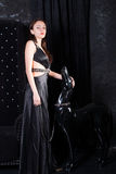 Woman in Black Dress with Dog Statue on Chain. Full Length of Woman Wearing Formal Black Dress Petting Dog Statue on Chain Stock Photo
