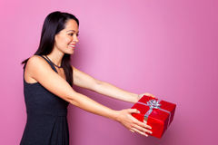 Woman in a black dress giving a present Stock Photography