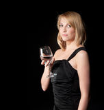 Woman in black dress  with glass over dark background Royalty Free Stock Photography