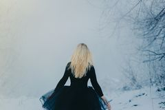 Woman in black dress goes back in the fog stock images