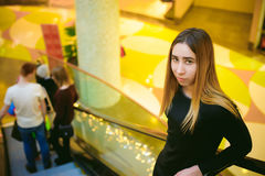 Woman in a black dress goes on the escalator at the mall Stock Photo