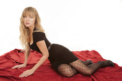 Woman black dress on hands on sheet. A woman in her black dress and fish net tights laying on a red sheet with a serious expression on her face Stock Photography